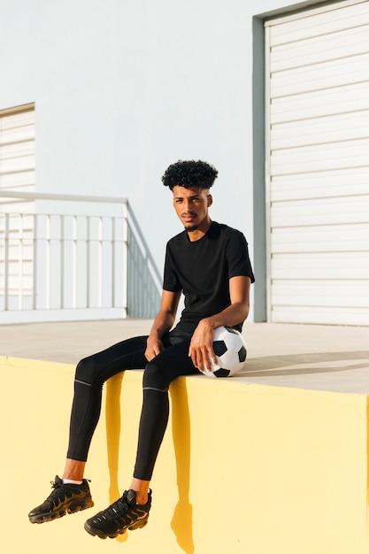 Jovem, étnico, sentando, com, bola futebol Foto gratuita