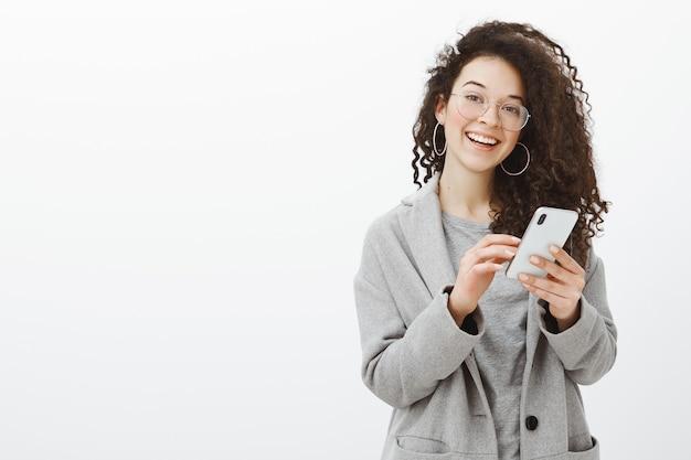 Jovem europeia alegre e emotiva de óculos e casaco cinza com brincos redondos elegantes Foto gratuita