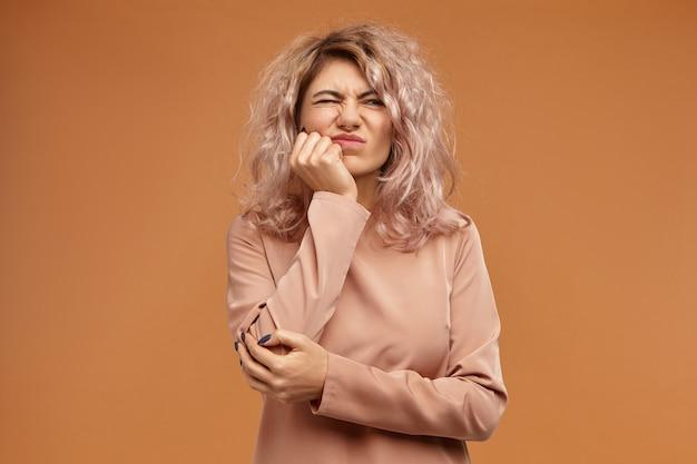 Jovem européia descontente com um penteado solto e bagunçado, expressão facial de tédio ou frustração, careta de dor e segurando a bochecha com a mão Foto gratuita