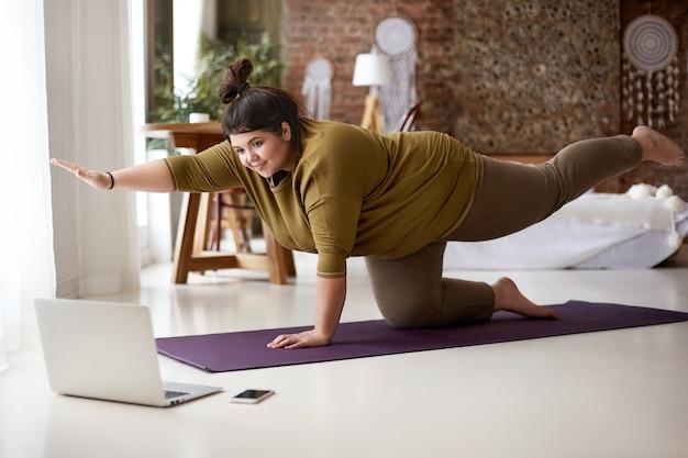 Jovem européia gordinha e obesa com nó no cabelo praticando ioga ou pilates dentro de casa no tapete, fazendo exercícios para fortalecer o núcleo, assistindo a vídeo aula on-line em frente a um laptop aberto no chão Foto gratuita