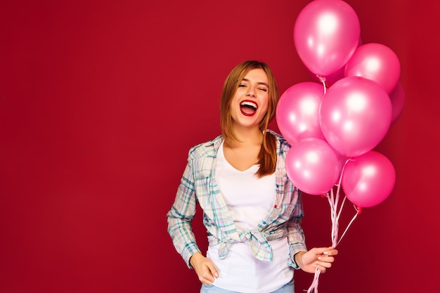 Jovem excitada posando com balões de ar rosa Foto gratuita
