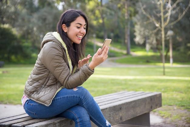 Jovem excitado conversando on-line no parque Foto gratuita