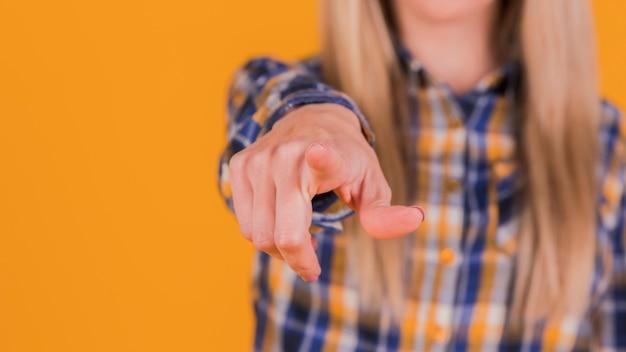 Jovem, executiva, apontar, seu, dedo, direção, câmera, contra, laranja, fundo Foto gratuita