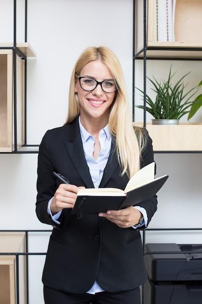 Jovem, executiva, com, agenda, ficar, em, modernos, escritório Foto Premium