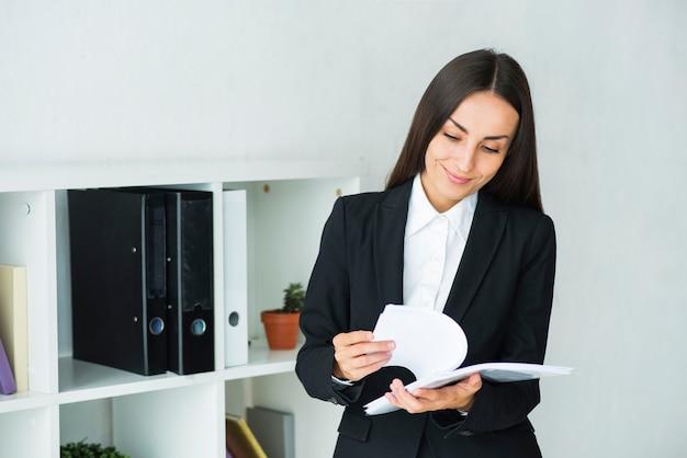 Jovem, executiva, examinando, a, documentos, em, escritório Foto gratuita