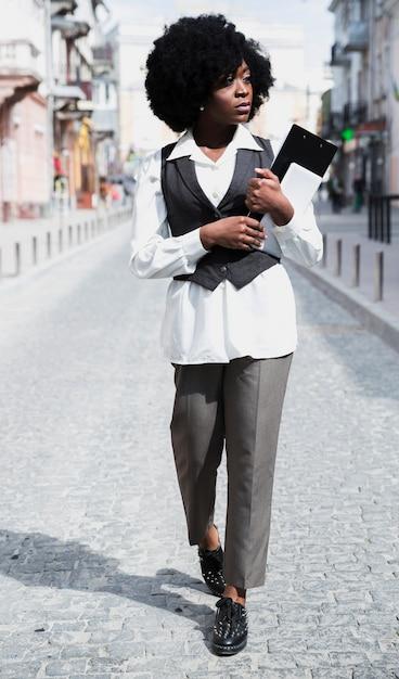 Jovem, executiva, segurando clipboard, e, tablete digital, em, mão, andar estrada Foto gratuita