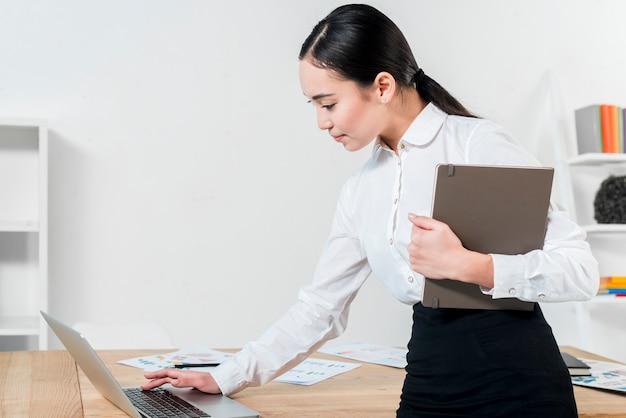 Jovem, executiva, segurando, diário, mão, usando, laptop, tabela, local trabalho Foto gratuita