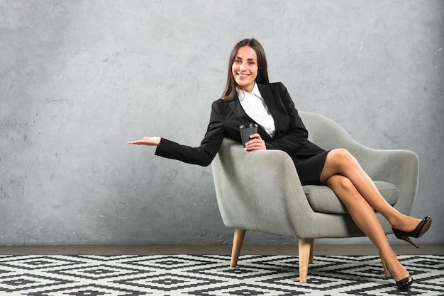 Jovem, executiva, sentando, poltrona, segurando, descartável, copo café, apresentando Foto gratuita