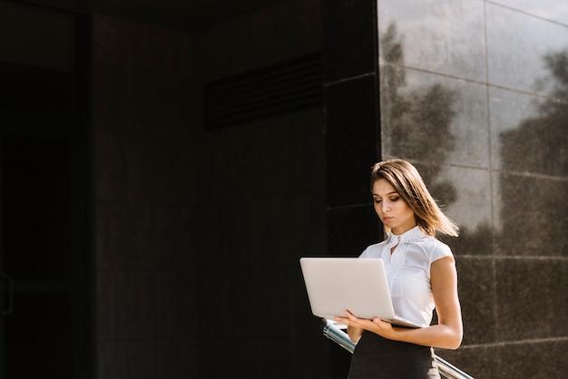 Jovem, executiva, usando, laptop, ficar, exterior, predios Foto gratuita