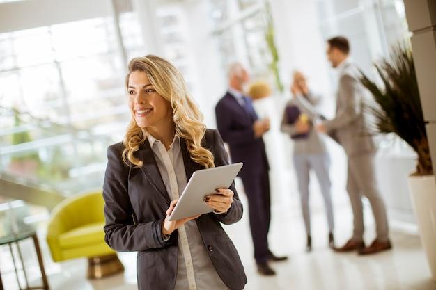 Jovem, executiva, usando, tabuleta, em, escritório, enquanto, outro, pessoas negócio, falando, em, fundo Foto Premium