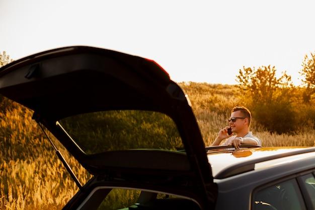 Jovem falando ao telefone perto de carro Foto gratuita