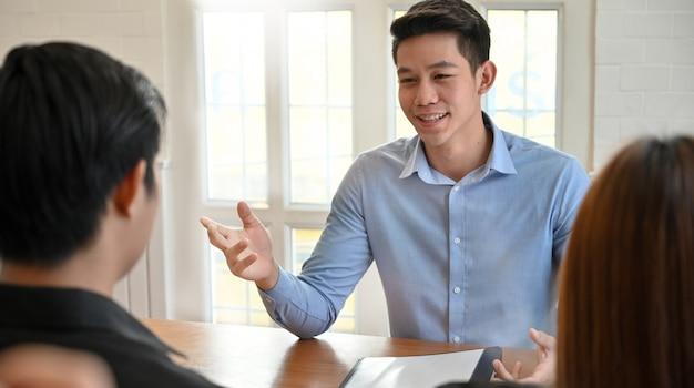 Jovem falando com trabalho de entrevista no escritório moderno. Foto Premium