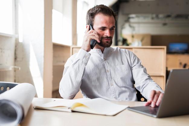 Jovem falando no celular enquanto trabalha no laptop Foto gratuita