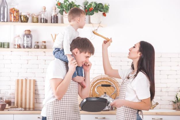 Jovem família cozinhando juntos. marido, esposa e seu bebê na cozinha. família amassar a massa com farinha. as pessoas cozinham o jantar ou café da manhã. Foto Premium