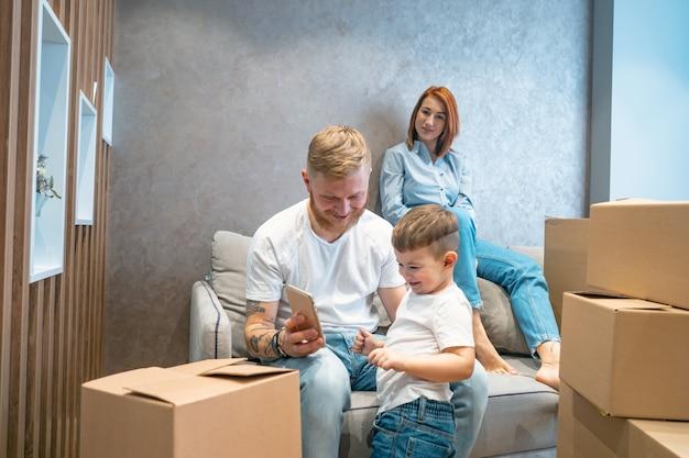 Jovem família feliz com criança desembalar caixas juntas, sentado no sofá Foto gratuita