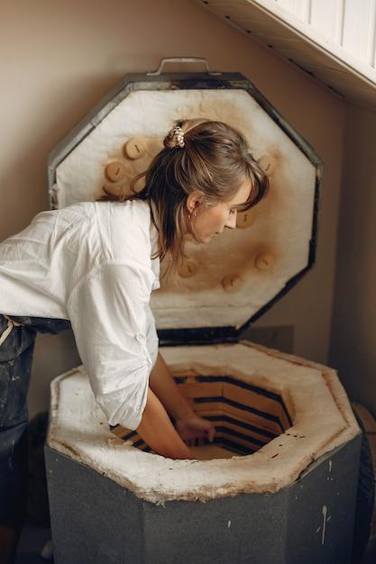 Jovem faz cerâmica na oficina Foto gratuita