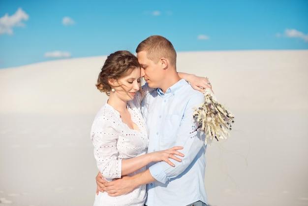 Jovem faz proposta de casamento com a namorada para um encontro romântico ao ar livre nas dunas de areia. Foto Premium