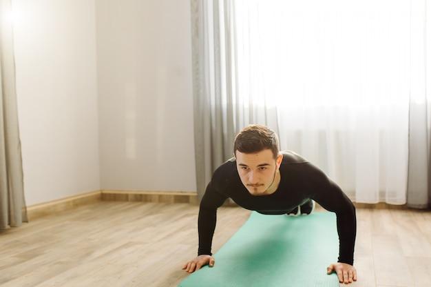 Jovem fazendo esporte exercícios em casa Foto gratuita