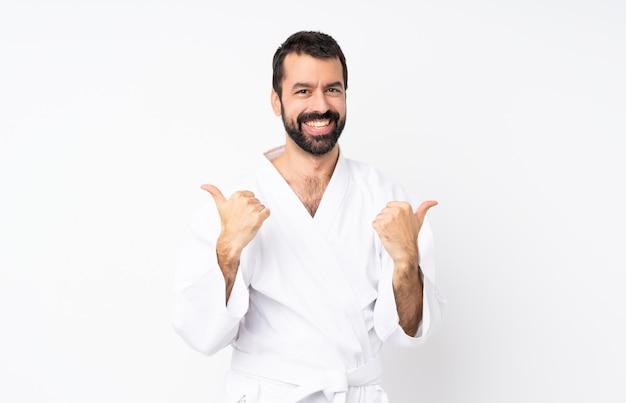 Jovem fazendo karatê sobre fundo branco isolado com polegares para cima gesto e sorrindo Foto Premium