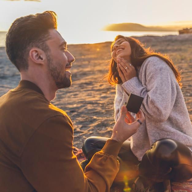 Jovem fazendo proposta para mulher na costa do mar de areia Foto gratuita