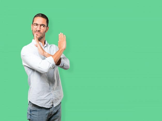 Jovem fazendo um gesto de não cruzar com os braços Foto Premium