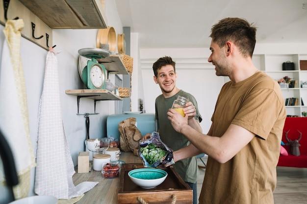 Jovem feliz ajudando uns aos outros para preparar o café da manhã em casa Foto gratuita
