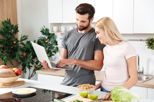 Jovem feliz amando o casal dançando na cozinha e cozinhar Foto gratuita