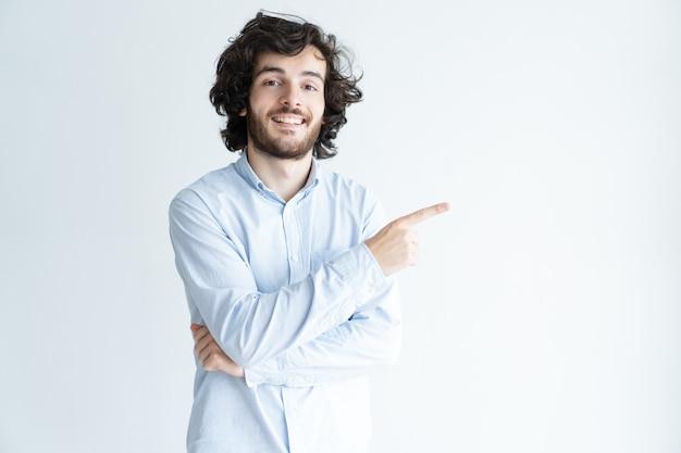 Jovem feliz, apontando o dedo de lado Foto gratuita
