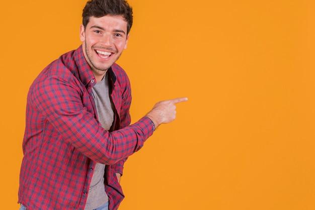 Jovem feliz apontando o dedo em um fundo laranja Foto gratuita