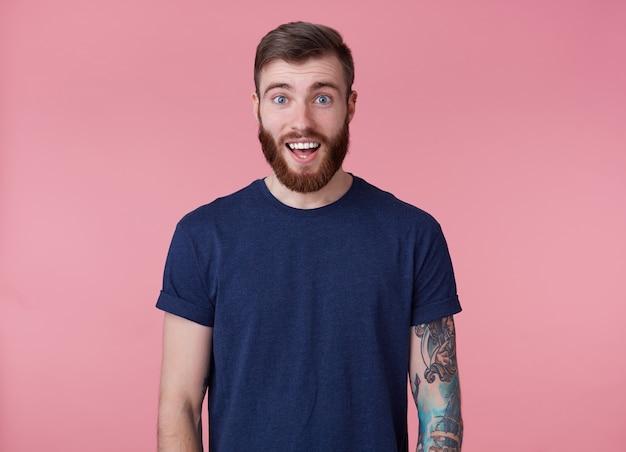 Jovem feliz atraente jovem de barba vermelha, vestindo uma camiseta azul, olhando para a câmera com a boca bem aberta e os olhos surpresos, viu algo fofo, isolado sobre fundo rosa. Foto gratuita