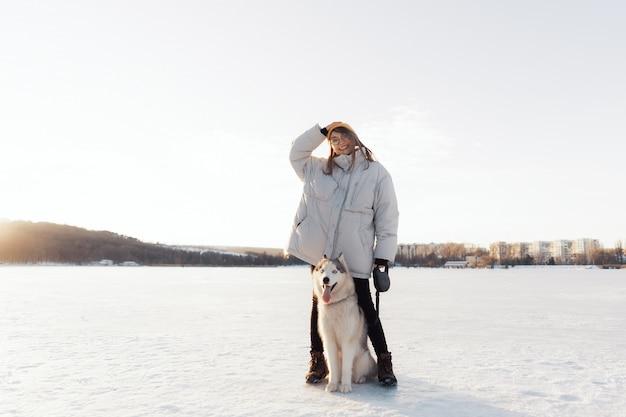 Jovem feliz brincando com cachorro husky siberiano em winter park Foto gratuita
