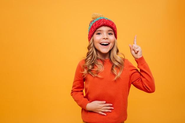 Jovem feliz com fome de suéter e chapéu segurando a barriga e ter idéia enquanto olha para a câmera sobre laranja Foto gratuita