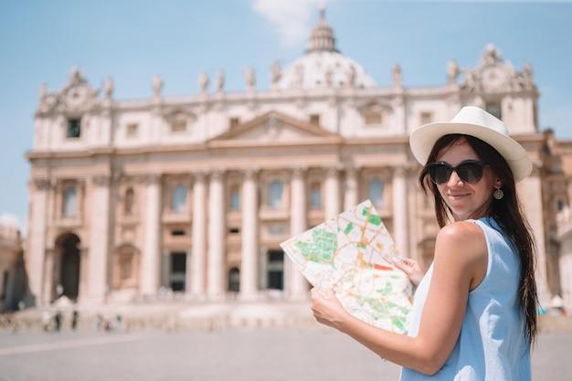 Jovem feliz com mapa da cidade na cidade do vaticano e a igreja da basílica de são pedro Foto Premium