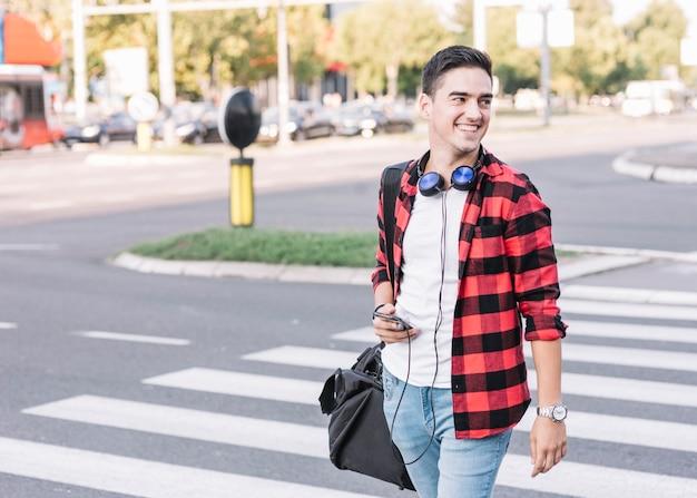 Jovem feliz com rua de cruzamento de celular Foto gratuita