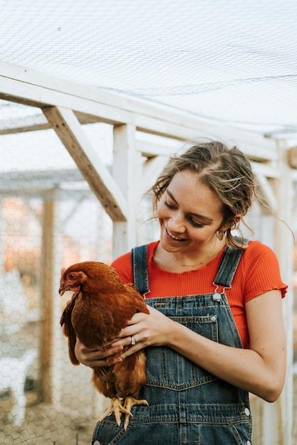Jovem feliz com uma galinha marrom Foto gratuita