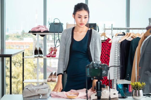 Jovem feliz da ásia ao vivo blog de vídeo (vlogger) e roupas de vendas no comércio eletrônico on-line, compras na loja. Foto Premium