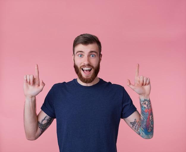 Jovem feliz de barba ruiva, com a boca escancarada de surpresa, quer chamar sua atenção apontando os dedos para cima para copiar o espaço isolado sobre o fundo rosa. Foto gratuita