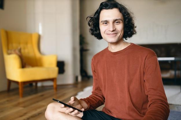 Jovem feliz do sexo masculino com cabelo preto ondulado, aproveitando a comunicação online usando uma conexão de internet sem fio de alta velocidade no telefone inteligente Foto gratuita