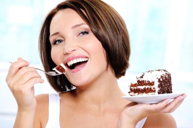 Jovem feliz e fofa comendo um bolo Foto gratuita