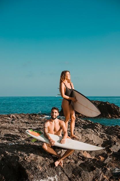 Jovem feliz e mulher com pranchas de surf na rocha perto do mar Foto gratuita