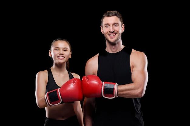 Jovem feliz e mulher em trajes esportivos olhando para você com sorrisos enquanto se tocam com as mãos em luvas de boxe Foto Premium