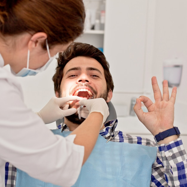 Jovem feliz e mulher em um exame dentário no dentista Foto Premium