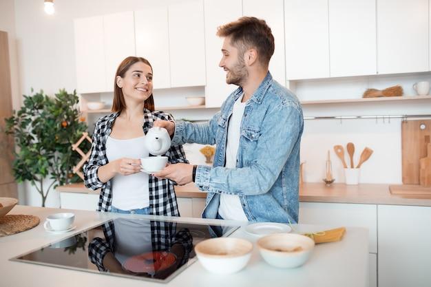 Jovem feliz e mulher na cozinha, café da manhã, casal juntos pela manhã, sorrindo, tomando chá Foto gratuita