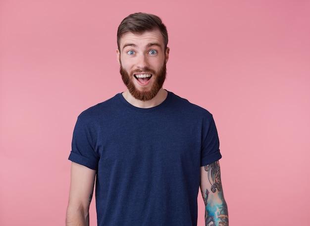 Jovem feliz espantado jovem atraente de barba vermelha com olhos azuis, vestindo uma camiseta azul, olhando para a câmera com a boca escancarada em surpresa isolada sobre fundo rosa. Foto gratuita