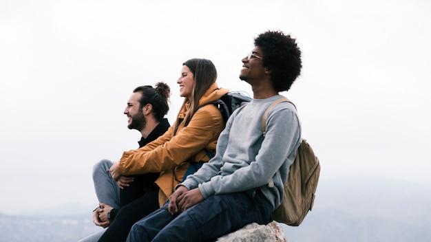 Jovem, feliz, macho fêmea, hiker, sentando, ligado, rocha, contra, céu Foto gratuita