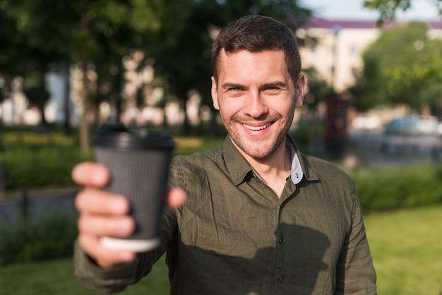 Jovem feliz mostrando o copo de café descartável no parque Foto gratuita