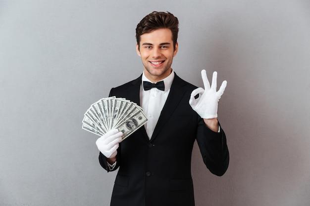 Jovem feliz mostrando o gesto bem segurando dinheiro. Foto gratuita
