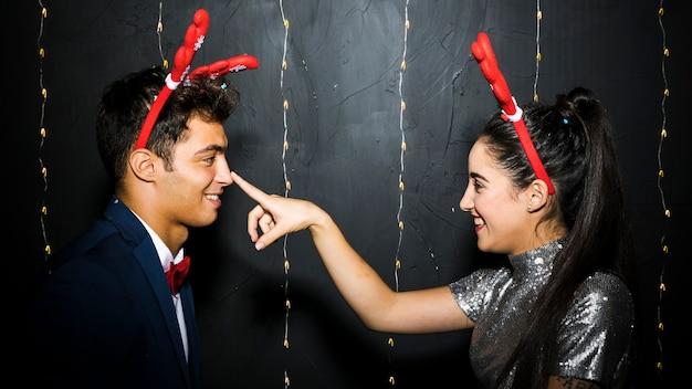 Jovem, feliz, par, com, veado vermelho, antlers, headbands Foto gratuita