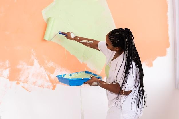 Jovem feliz pinta a parede com tinta Foto Premium