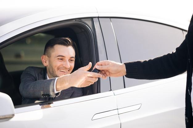 Jovem feliz recebendo as chaves do carro para seu novo automóvel Foto Premium